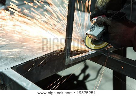 Close-up of hands of craftsman with grinding machine. He is wearing protective industrial gloves while using professional tool to cut piece of metal with many sharp sparks. Copy space in the left side