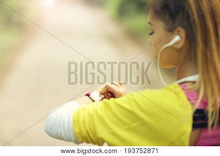 Woman jogging in the forest and setting smart watch