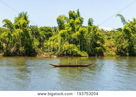 Ivoloina Madagascar - December 22 2015: Malagasy countryside people from village transport freight by Traditional handmade dugout wooden boat near the city of Toamasina (Tamatave) Madagascar East Africa. Everyday life on the river.