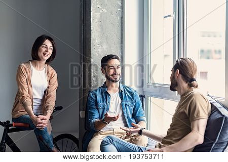Merry freelancers are taking comfortable places and talking with each other. They looking at interlocutors with interested smile