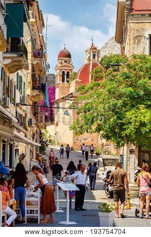 CORFU ISLAND, GREECE - JUNE 26, 2017: Narrow tourist street with people walking. Corfu city, Greece. Daylight view