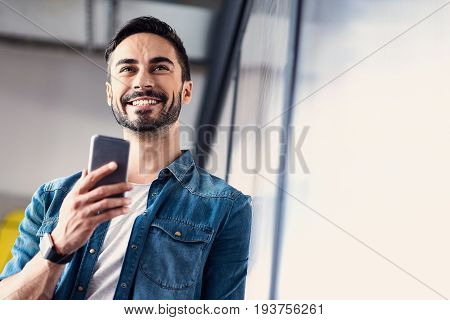 Happy male freelancer is using smartphone for work and looking ahead with bright smile. He leaning against wall. Low angle and copy space. Portrait