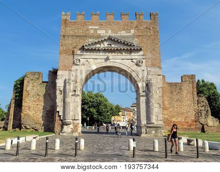 Rimini Italy - June 21 2017: Unidentified people walk under Augustus Arch - the ancient romanesque gate and the historical landmark of Rimini Italy.