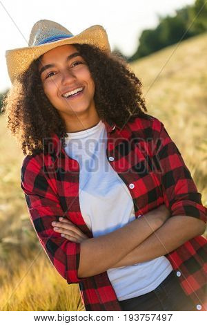 Portrait of beautiful and happy mixed race African American female girl child wearing straw cowboy hat, plaid shirt and white t-shirt, smiling with perfect teeth in a wheat or barley field at sunset