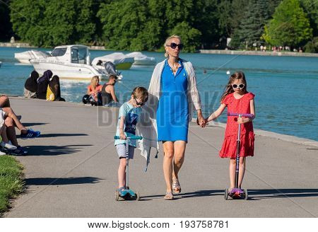Happy Family Walking On Annecy Lake Embankment. Haute-savoie, France
