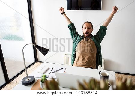 Weary freelancer is yawning and stretching. He sitting at workplace. Portrait