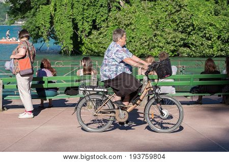 Senior Woman Ride On Her Bicycle At Park On Annecy Lake. Haute-savoie, France