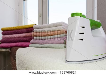 Ironing Linen With Steam Generator. A Stack Of Ironed Towels Lying Next To The Iron. Teflon Sole Pla