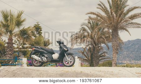 Scooter Parked At Sunny Day Under The Palm Trees Of A Beautiful Beach In Crete Island