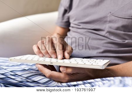 closeup of a young caucasian man in pajamas sitting in a comfortable armchair typing in a computer keyboard