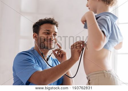 Keep smiling. Attentive male person in special uniform using stethoscope while checking heart of his young patient and foreseeing good result