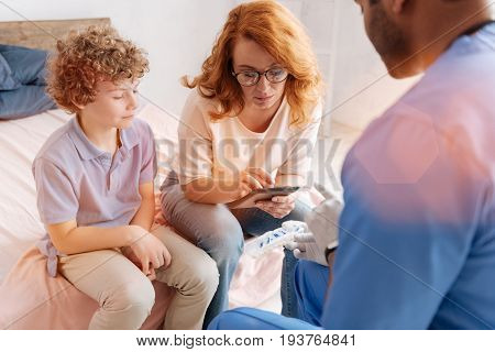 Make some notes. Serious woman wearing glasses and sitting in front of medical worker while typing prescription on her tablet