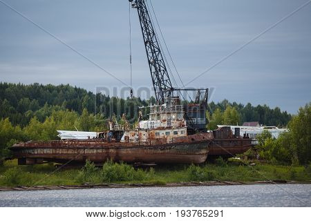 Rusty trawler wreck on river coat in russia