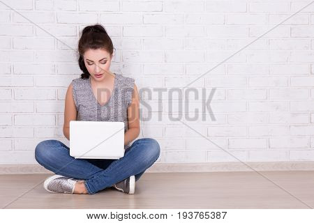 Beautiful Woman Sitting On The Floor With Laptop And Space Over White Wall