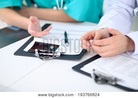 Female doctor and young surgeon intern in hospital.