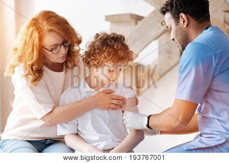 Feel discomfort. Kind mother bowing her head while rolling up sleeve of the T-shirt of her son while supporting him
