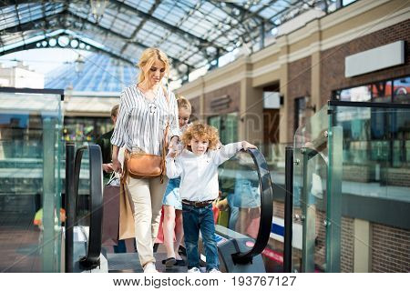 mother and kids mother with kids rising on escalator with shopping bags in mall