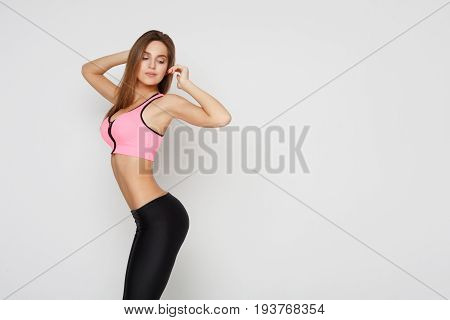 Beautiful fitness girl posing on studio background. Portrait of confident sporty woman with perfect body, healthy lifestyle and bodycare concept