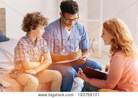 What is my diagnosis. Positive delighted woman with curly hair sitting in semi position and holding her notebook while looking at her son