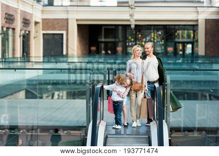 Happy Young Family Holding Shopping Bags While Standing Together On Escalator