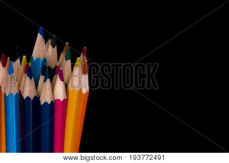 Colored pencils in the lower left corner on a black background. Selective focus