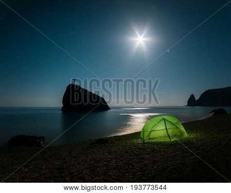 Tent on the beach with rocks and a night sky with stars. Fiolent. Crimea.