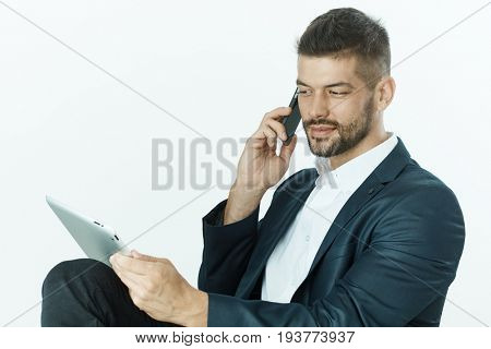 Businessman on phone using tablet computer isolated stock photo.