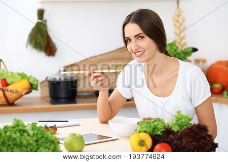 Beautiful  Hispanic woman is cooking in the kitchen. Housewife is tasting fresh salad while sitting at the table