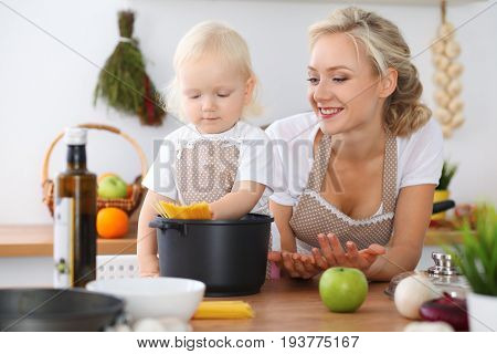 Happy family in the kitchen. Mother and child daughter  cooking pasta for the breakfast