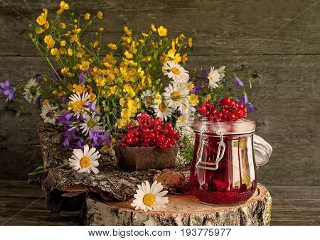 The juice from the berries of viburnum in glass containers on a napkin next to a bouquet of wild flowers on a wooden stand. Rustic. A horizontal frame.