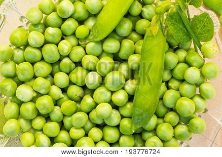 Green peas in a glass plate on a light wooden background close-up