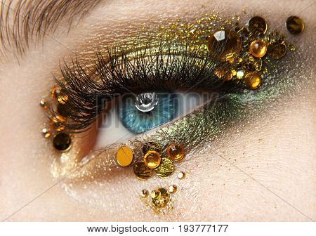 Macro And Close-up Creative Make-up Theme: Beautiful Female Eye With Golden Shadows And Yellow Diamo