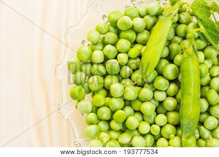 Green peas in a glass plate on a light wooden background