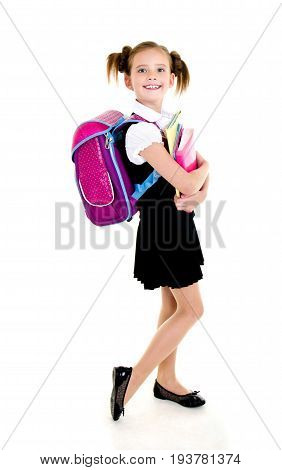 Portrait of smiling happy school girl child with backpack and books in uniform isolated on a white background