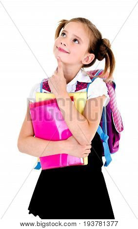 Portrait of thinking dreaming school girl child with backpack and books in uniform isolated on a white background