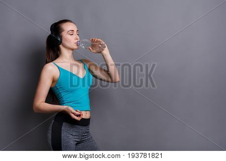 Young sport woman drinking water from plastic bottle, thirsty after training, healthy lifestyle concept. Gray background