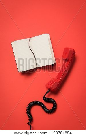 Close-up View Of Telephone Handset And Blank Open Notebook Isolated On Red