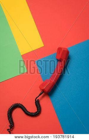 Close-up View Of Red Telephone Handset With Curly Cord On Bright Background