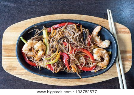Wok spaghetti with red and green peppers and shrimps. Restaurant food. Served with chinese chopsticks