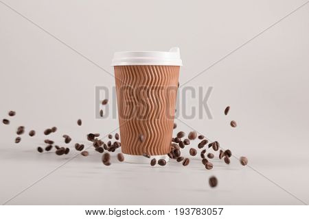 Disposable Coffee Cup With Falling Coffee Grains Isolated On Beige