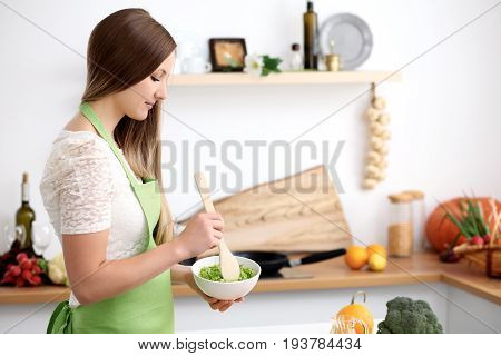 Young woman in the green apron cooking in the kitchen. Housewife slicing fresh salad.