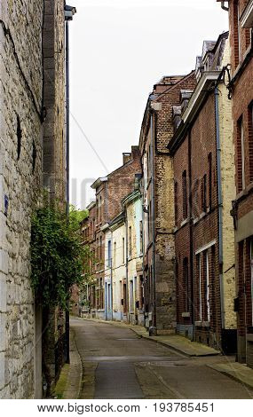 Obsolete Narrow Street with Multi Colored Old Houses in Cloudy Day Outdoors. Dinant Belgium