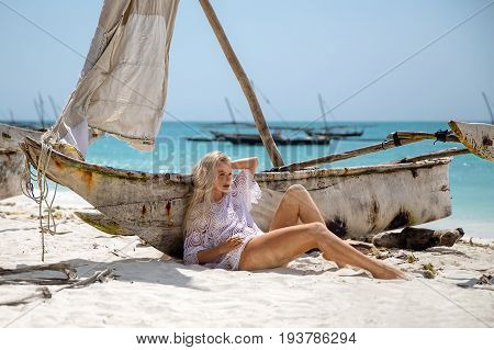 Beautiful blonde woman in the knitted white swimsuit sitting on the lonely beach with turquoise water and white sand near traditional fishing boat dhow. Zanzibar. Nungwi.