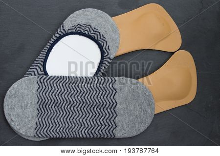 Leather Orthopedic Insoles With Socks. Stone Background. Top View.