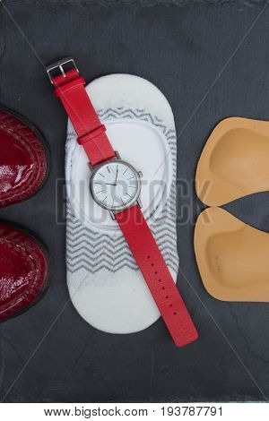 Leather Orthopedic Insoles, Socks, Wrist Watch And Red Shoes On Stone Background. Top View.