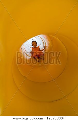 Little Asian girl playing slide at the playground