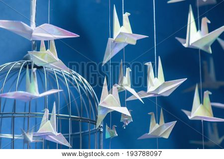 many Paper crane origamis on blue background