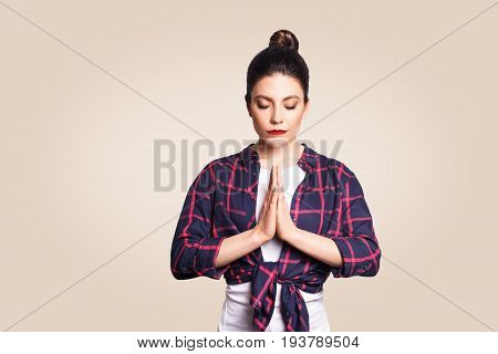 Young brunete woman practising yoga holding hands in namaste and keeping her eyes closed. Caucasian girl meditating indoors praying for peace and love having calm and peaceful facial expression.
