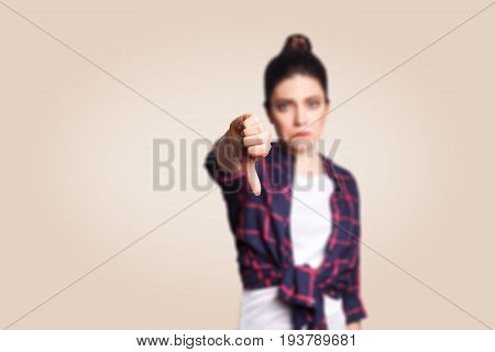 Dislike. Young unhappy upset girl with casual style and bun hair thumbs down her finger, on beige blank wall with copy space looking at camera with toothy smile. focus on finger.