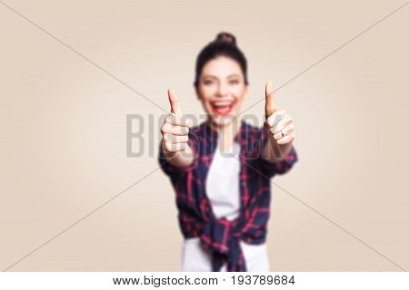 Young happy girl with casual style and bun hair thumbs up her finger, on beige blank wall with copy space looking at camera with toothy smile. focus on finger.